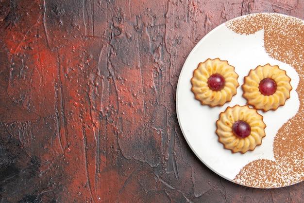 暗いテーブルケーキの甘いビスケットのプレート内のおいしい小さなクッキーの上面図