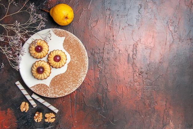 어두운 테이블 케이크 달콤한 비스킷 설탕에 접시 안에 상위 뷰 맛있는 작은 쿠키