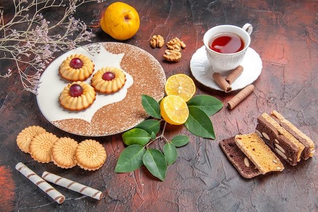 어두운 테이블 설탕 케이크 달콤한 비스킷에 차 한잔과 함께 상위 뷰 맛있는 작은 쿠키