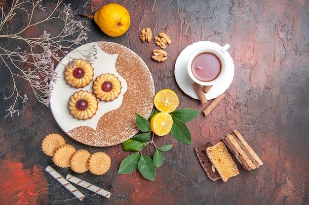 Вид сверху вкусное маленькое печенье с чашкой чая на темном столе, сахарный торт, сладкое печенье