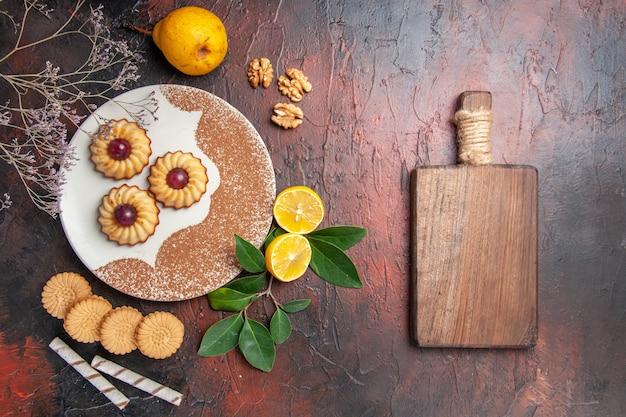 Vista dall'alto gustosi piccoli biscotti con frutta sul biscotto dolce torta di zucchero da tavola scuro