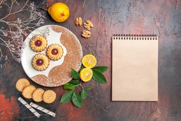 어두운 테이블 설탕 케이크 달콤한 비스킷에 과일과 함께 상위 뷰 맛있는 작은 쿠키