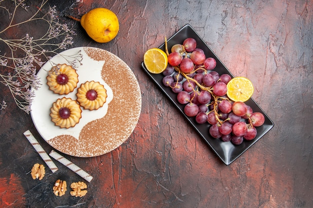 Top view yummy little cookies with grapes on dark table cake sweet biscuit sugar