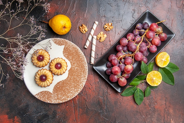 Top view yummy little cookies with grapes on dark table, cake sweet biscuit sugar