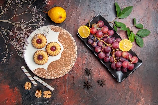 Вид сверху вкусное маленькое печенье с виноградом на темном столе, торт, сладкое печенье, сахар