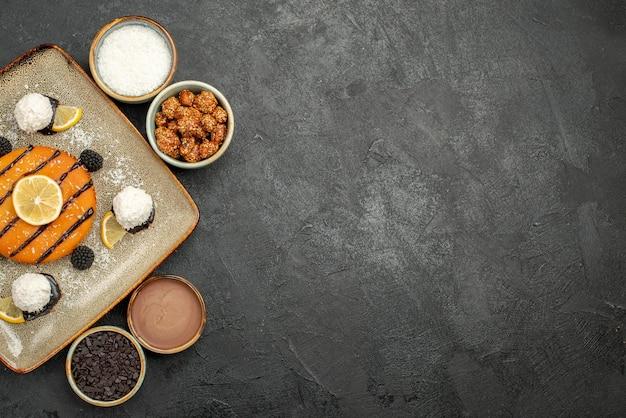 Vista dall'alto squisita piccola torta con caramelle al cocco su una superficie grigio scuro torta biscotto tè biscotto dolce