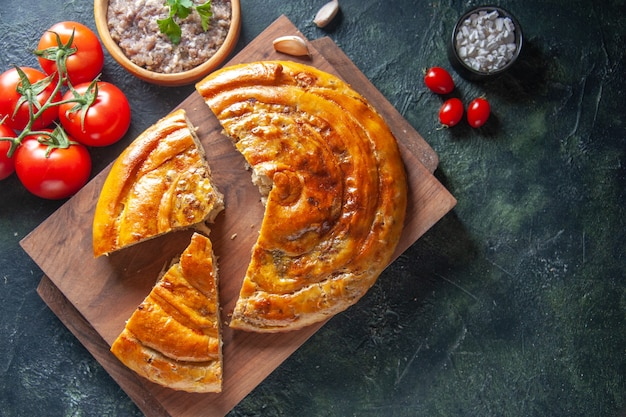 Top view of yummy meat pie with red tomatoes on dark surface