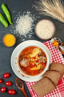 Zuppa di carne gustosa vista dall'alto con pane e pomodori su sfondo scuro