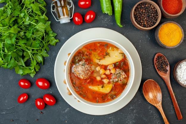 Zuppa di carne gustosa vista dall'alto con verdure e condimenti su sfondo scuro