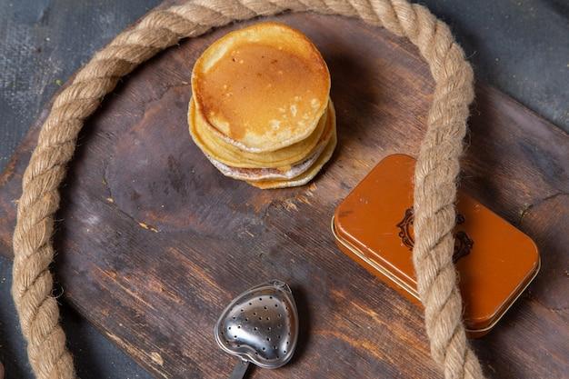 Vista dall'alto gustosissimi muffin al forno e deliziosi con corde sulla scrivania in legno e sfondo grigio cibo pasto colazione dolce