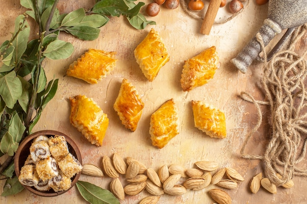 Top view yummy nut pastries with fresh nuts on wooden desk