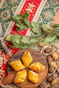 Vista dall'alto di squisiti pasticcini a base di noci con noci fresche sulla scrivania marrone