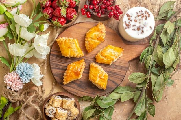 木製の机の上の果物とトップビューおいしいナッツペストリー