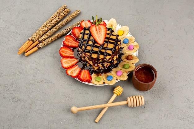 상위 뷰 맛있는 팬케이크 초콜렛 팬케이크 빨간 얇게 썬 딸기와 바나나 회색 배경에 흰색 접시 안에