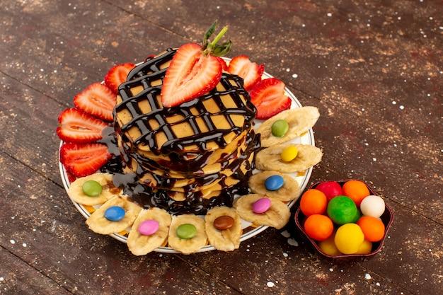 茶色の木製の机の上の新鮮なフルーツとチョコレートのおいしいおいしいパンケーキのトップビュー