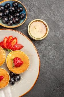 灰色の机の上の果物で少し形成されたおいしいパンケーキの上面図パイフルーツケーキ