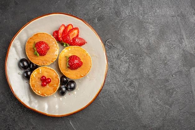 暗闇の中で果物で少し形成された上面図おいしいパンケーキ