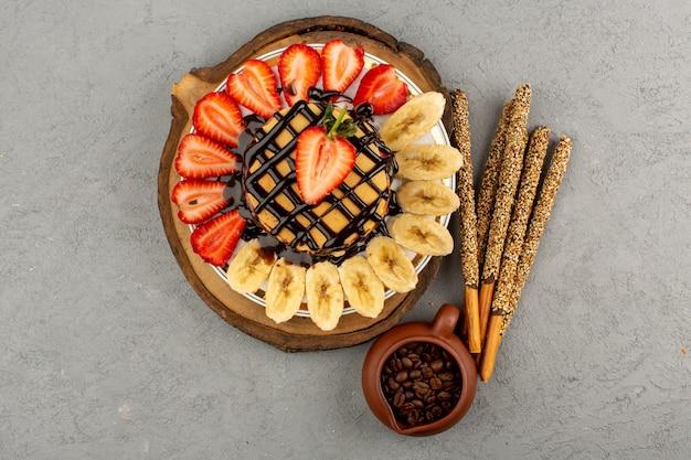 Вид сверху вкусные блины сладкие вкусные с нарезанной красной клубникой и бананами внутри тарелки на сером фоне