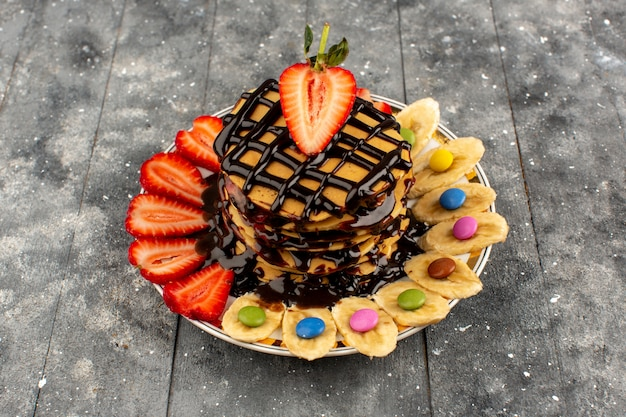 Вид сверху вкусные блины сладкие вкусные с нарезанной красной клубникой и бананами на сером полу