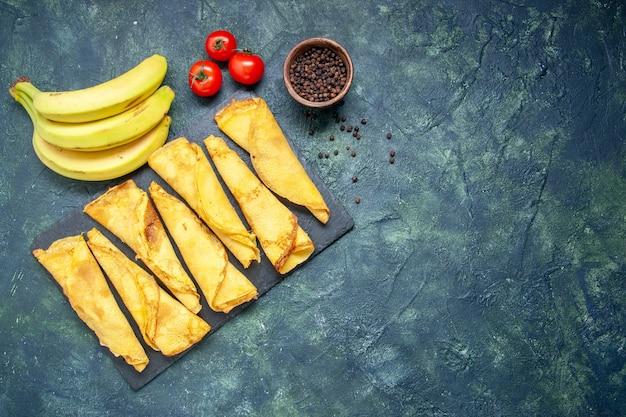 Vista dall'alto deliziose frittelle con banane su sfondo scuro pasta per torta hotcake farina colorata pasticceria torta dolce carne