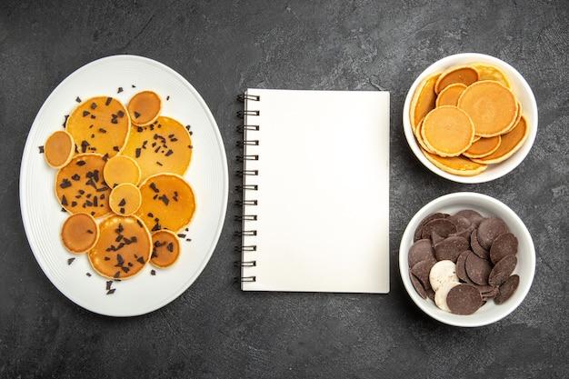 어두운 배경에 초코 칩과 쿠키가있는 상위 뷰 맛있는 팬케이크