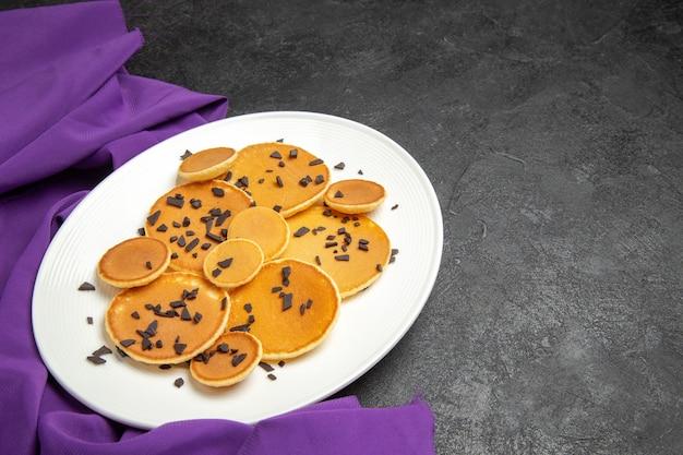 어두운 책상에 초코 칩을 곁들인 상위 뷰 맛있는 팬케이크