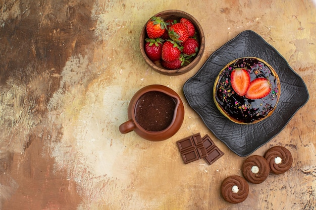 Вид сверху вкусные блины с печеньем и фруктами на деревянном столе