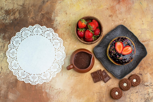 Top view yummy pancakes with cookies and fruits on wooden desk