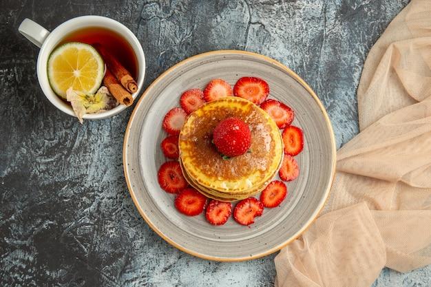 光の上のお茶と果物のカップとおいしいパンケーキの上面図