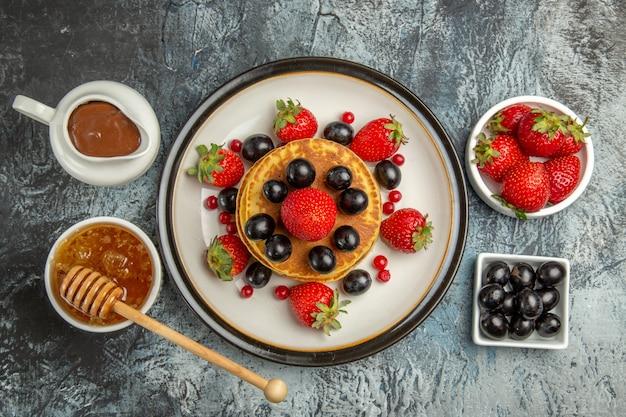 新鮮な果物と蜂蜜を光に当てた上面図おいしいパンケーキ