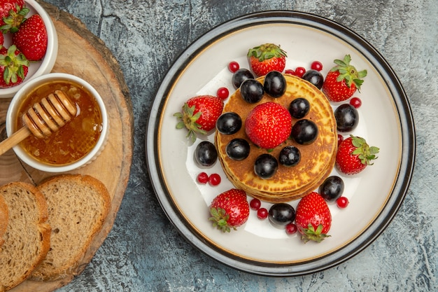 Top view yummy pancakes with fresh fruits and bread on light floor fruit cake sweet