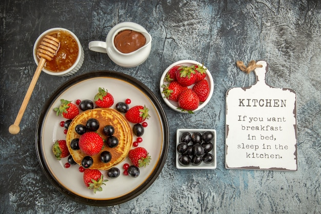 Top view yummy pancakes with fresh fruits and honey on light floor sweet fruit cake