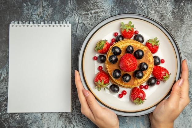 Vista dall'alto gustosi pancake con frutta fresca alla luce