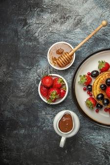 軽い机の上の新鮮な果物と甘いパンケーキの上面図フルーツケーキ甘い
