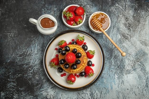 明るい床のフルーツケーキの甘い上に新鮮な果物とトップビューおいしいパンケーキ
