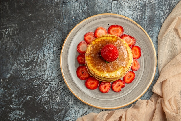 Top view yummy pancakes with fresh strawberries on light