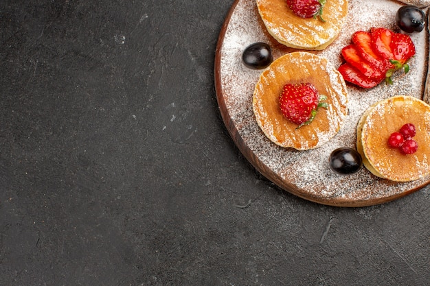 トップビューフルーツと暗い床の甘いフルーツケーキのケーキとおいしいパンケーキ