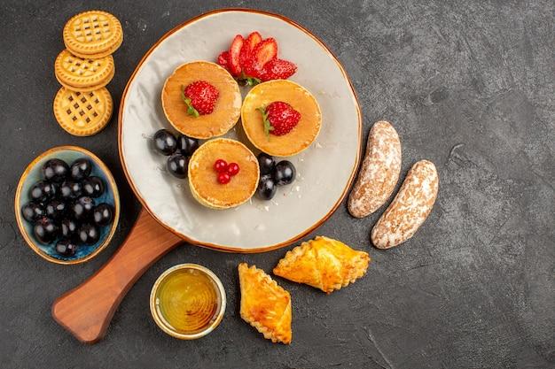 Вид сверху вкусные блины с фруктами и пирожными на темноте