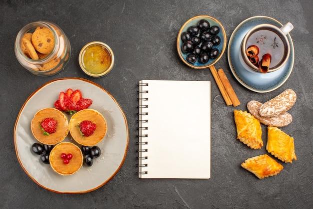 Вид сверху вкусные блины с фруктами и чашкой чая на темноте
