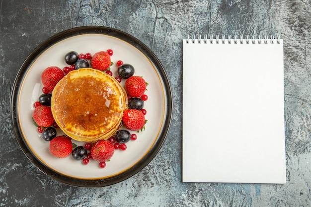 ライトデスクにフルーツと蜂蜜のトップビューおいしいパンケーキ