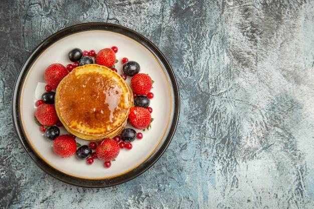 Вид сверху вкусные блины с фруктами и медом на светлом полу