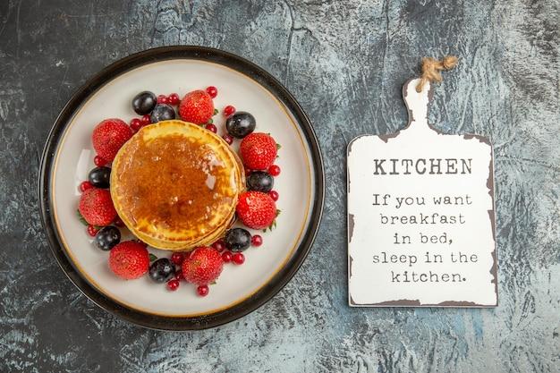 빛에 과일과 꿀을 곁들인 맛있는 팬케이크
