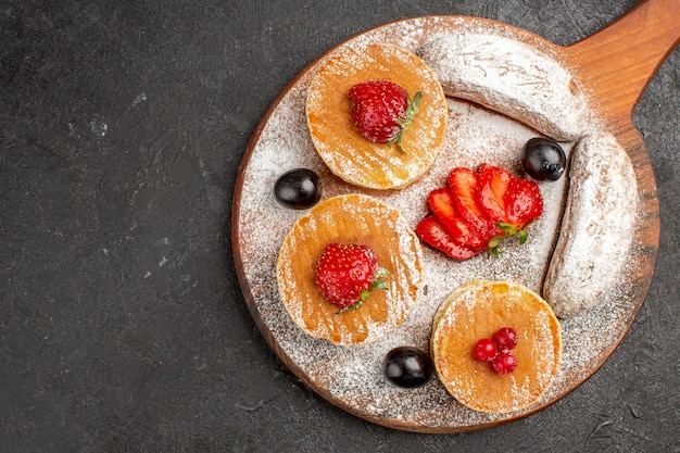 Top view yummy pancakes with fruits and cakes on a dark