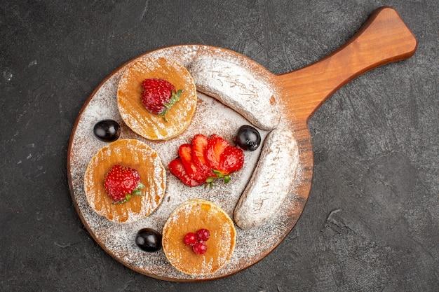 Vista dall'alto gustose frittelle con frutta e torte al buio