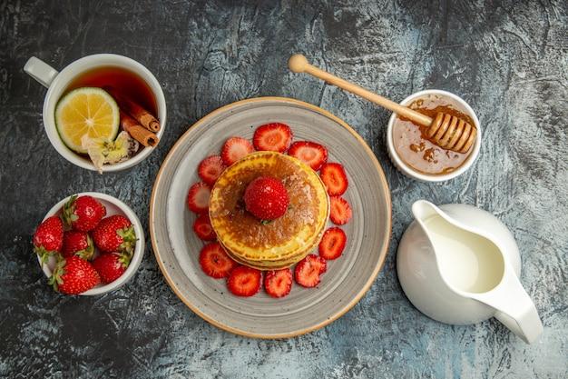 Vista dall'alto gustosi pancake con frutta e tazza di tè in luce