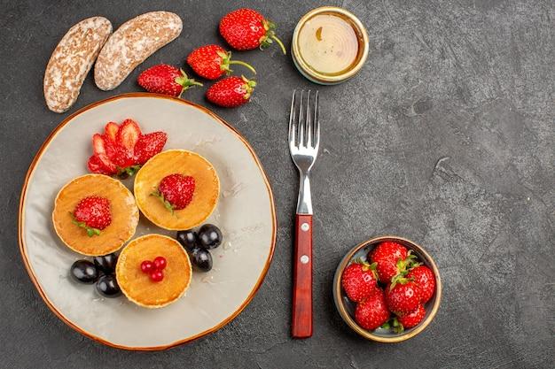 Vista dall'alto gustosi pancake con frutta al buio