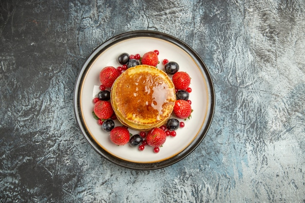 Top view yummy pancakes with fruits and honey on light