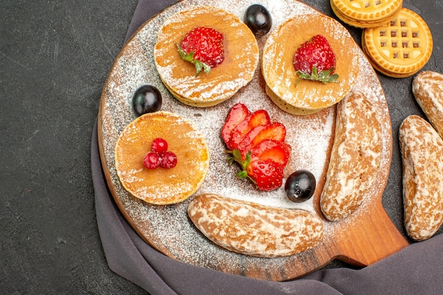 Top view yummy pancakes with fruits and sweet cakes on dark desk