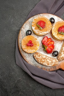Top view yummy pancakes with fruits and sweet cakes on dark floor