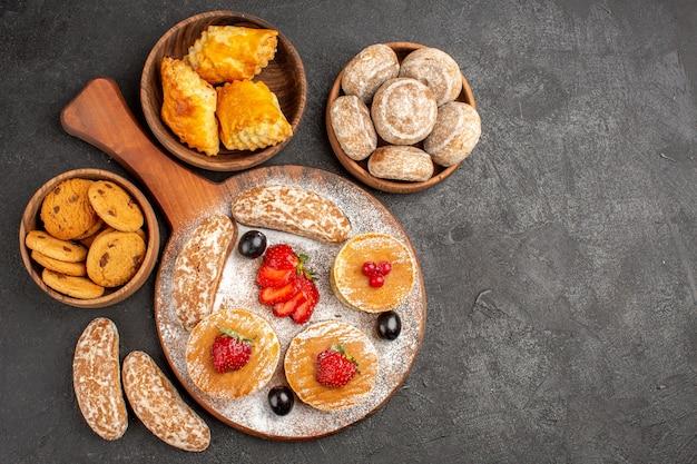 Vista dall'alto gustose frittelle con frutta e torte dolci al buio